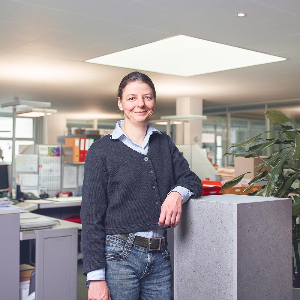 Myriam Rohr steht an ihrem Arbeitsplatz und lächelt in die Kamera.