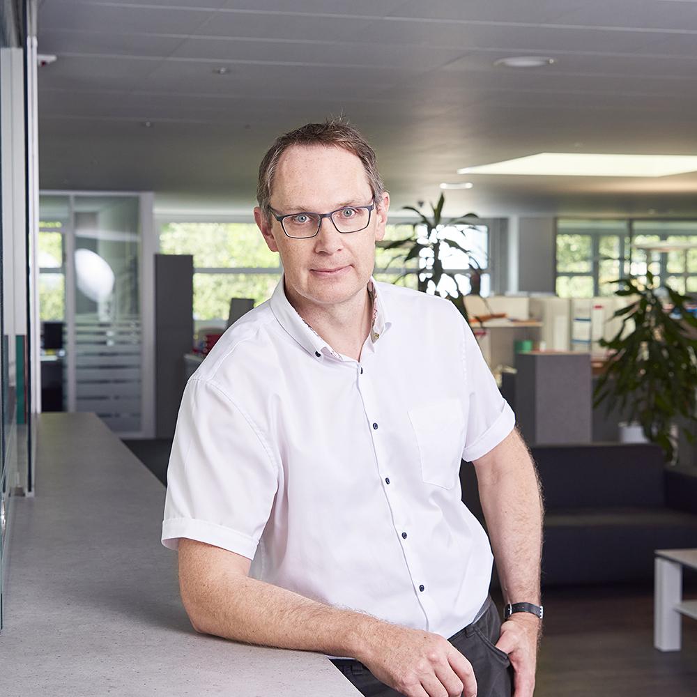 Der Geschäftsleiter Patrick Lerchmüller steht im Büro an einer Ablage angelehnt.