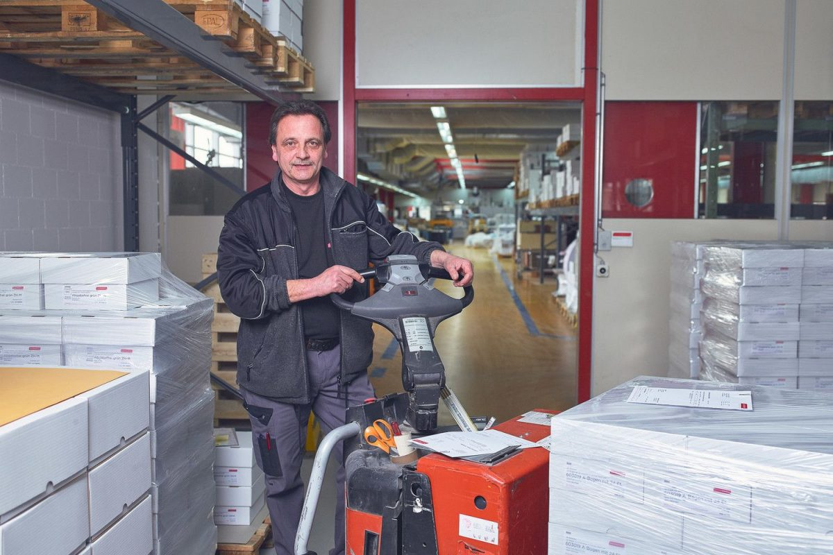 Unser Lagermitarbeiter umgeben von Druckerzeugnissen bei der Warenauslieferung.