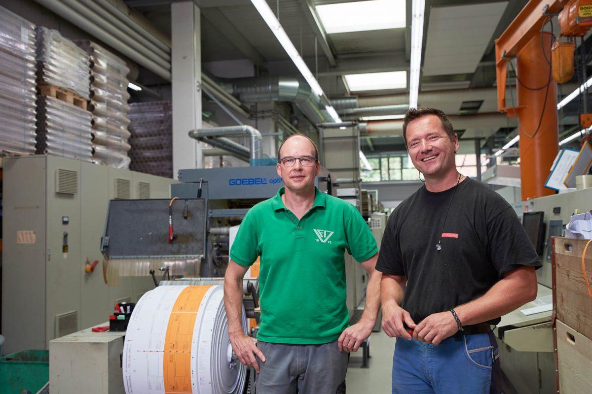 Zwei Mitarbeiter der Druckerei vor ihren Druckmaschinen.