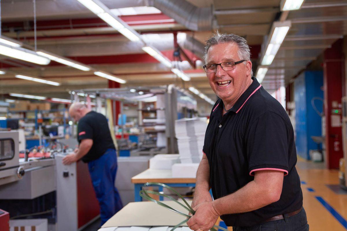 Druckmitarbeiter an seinem Arbeitsplatz beim abbinden der Schachteln mit Druckerzeugnissen.
