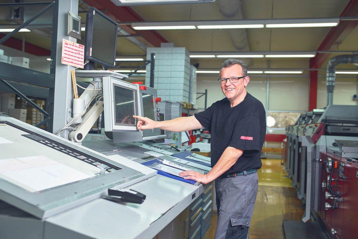 Mitarbeiter bei der Bedienung einer Druckmaschine.