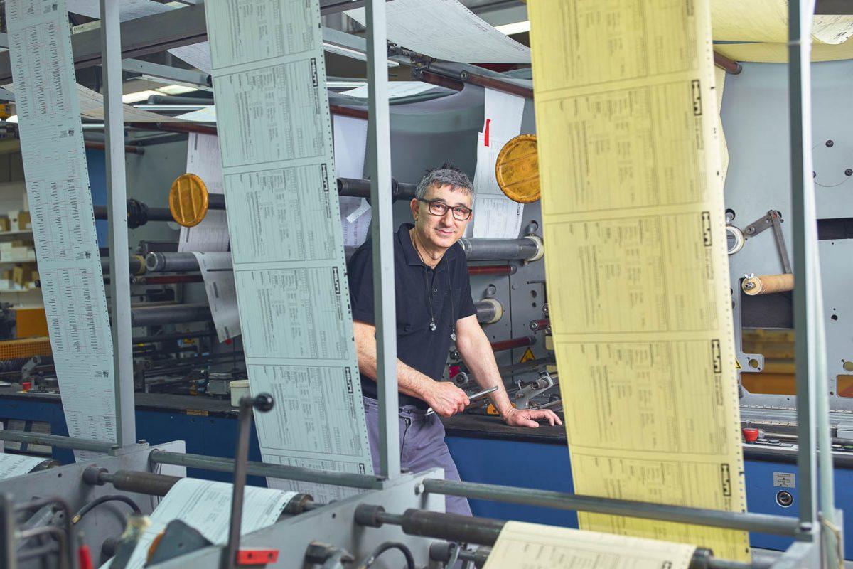 Mitarbeiter bei der Weiterverarbeitung einer Durchschreibegarnitur.