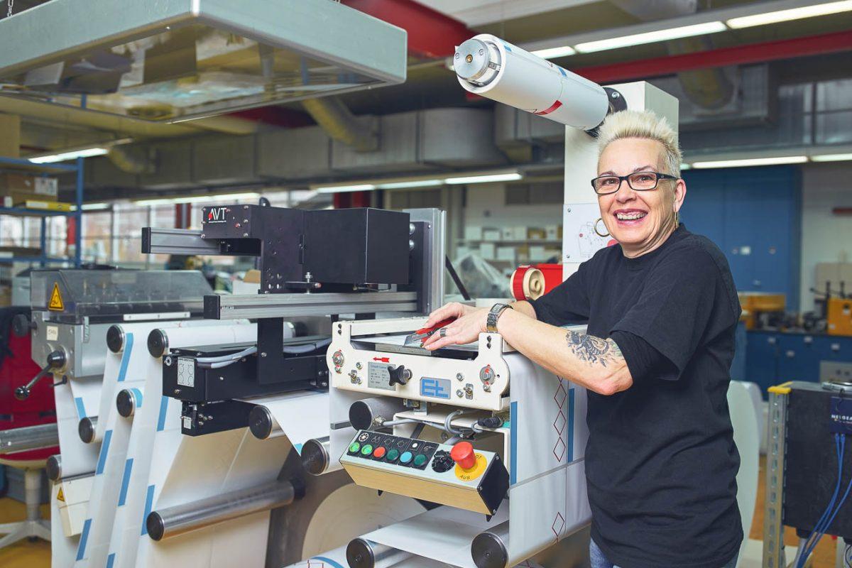 Mitarbeiterin in der Produktion bei der Weiterverarbeitung eines Druckerzeignisses.
