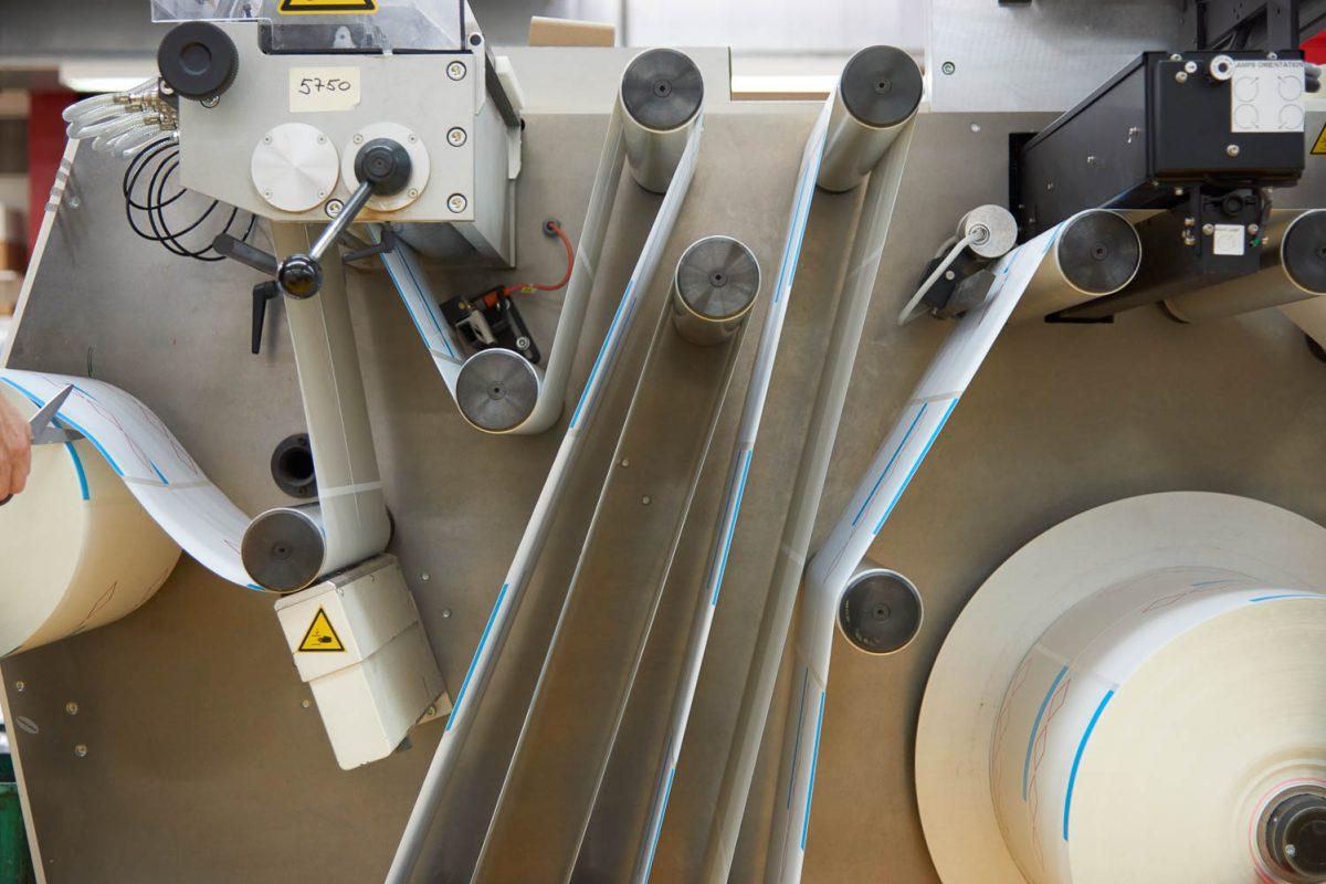 Ein Druckerzeugniss eingepsannt in der Maschine während der Produktion.