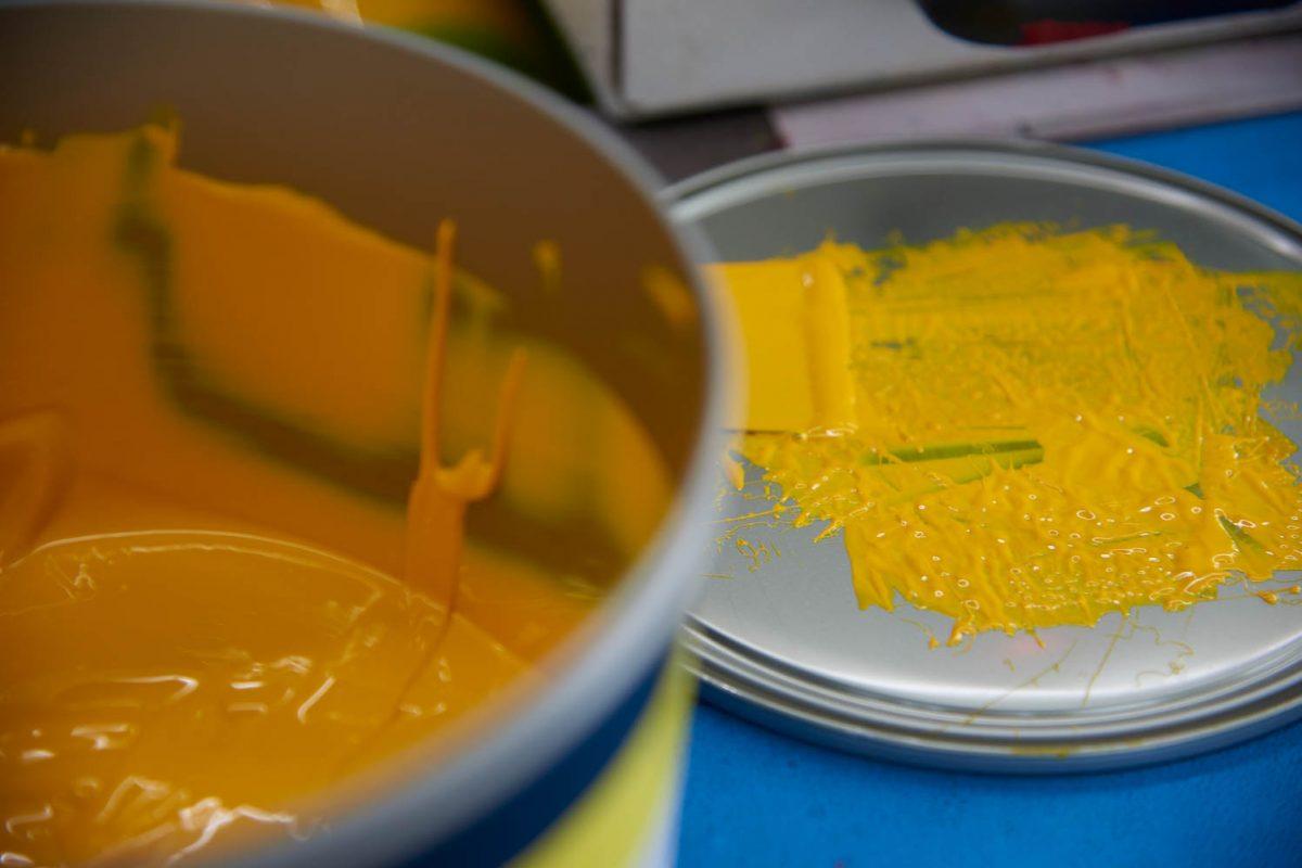 Ein Farbeimer und Deckel mit gelber Druckfarbe.