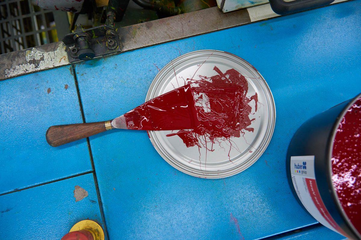 Ein Farbspachtel von oben, welcher voll mit roter Farbe ist.