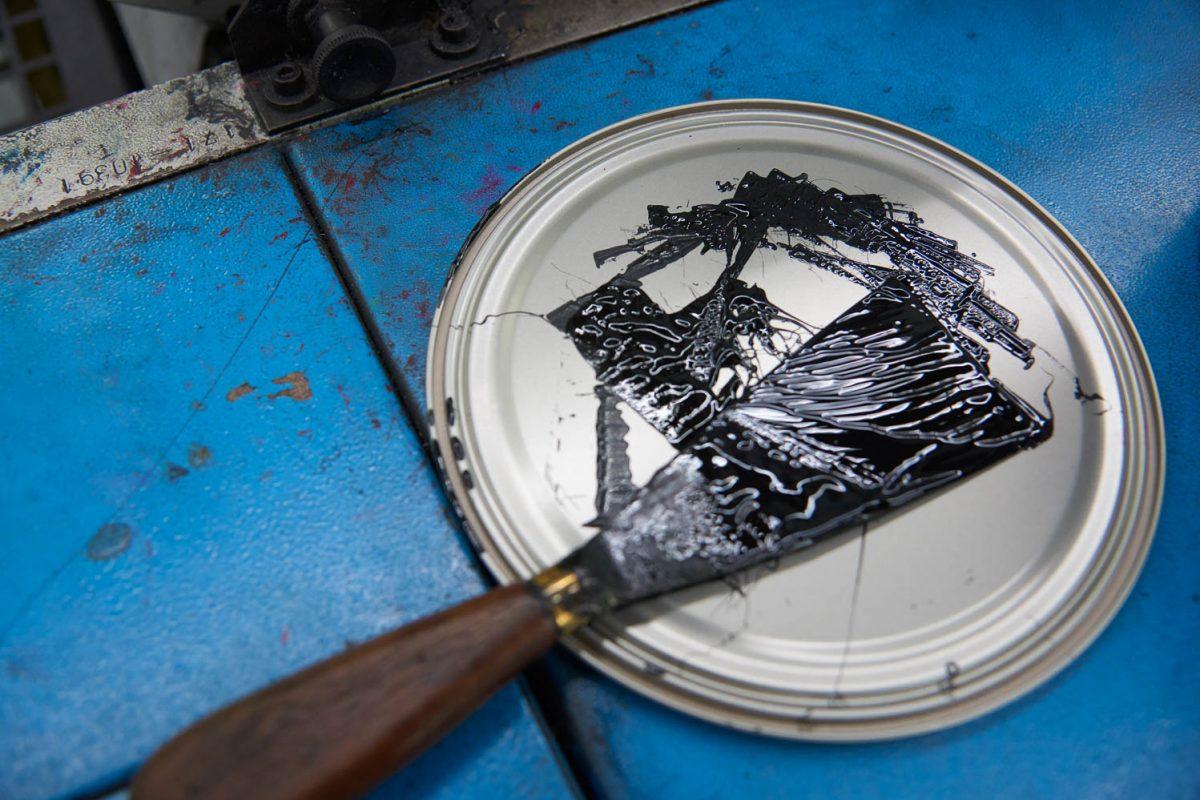 Ein Farbspachtel mit schwarzer Farbe drauf.