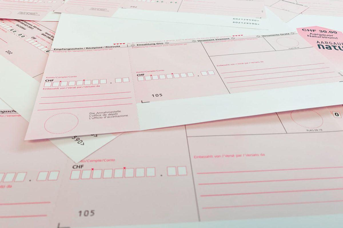 Rote Einzahlungsscheine verteilt auf einer Ablage zur Ansicht.